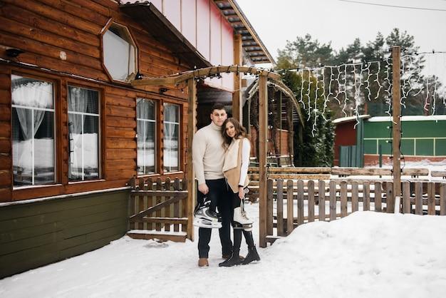 Winterliebesgeschichte auf eis. stilvoller kerl und mädchen mit schlittschuhen in der hand gehen eislaufen