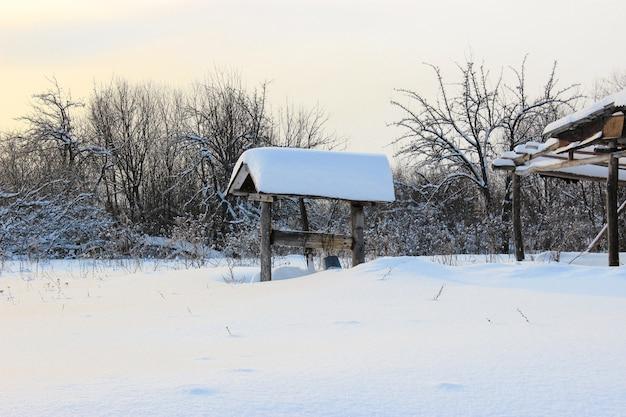 Wintermärchen im dorf mit schneebedeckten dächern, brunnen