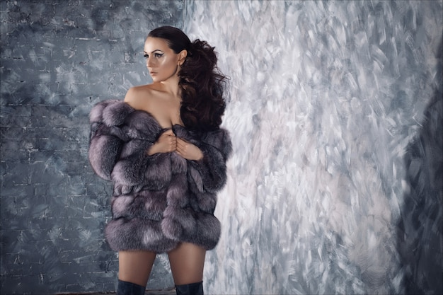 Wintermode-stil. schönheit im luxuspelzmantel auf nacktem körper mit overknee-stiefeln.