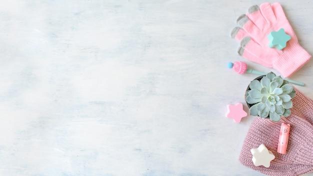 Wintermodell mit warm gestrickter rosafarbener kleidung, decke, saftig im topf, notizbuch