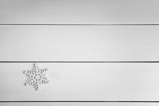 Winteroberfläche mit schneeflocke auf holzoberfläche