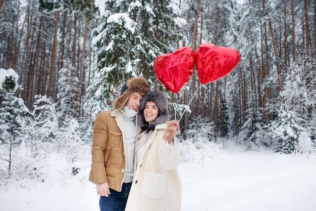 Winterpaar verliebt. jungen und mädchen umarmen im winter schnee und den feenwald mit luftballons.
