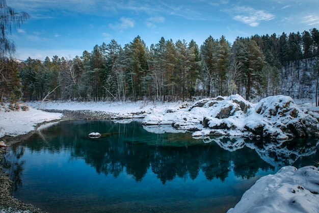 Winterpanorama, kleiner türkisfarbener see in den bergen zwischen schneebedecktem wald. bäume spiegeln sich im seewasser. majestätische natur des altai-gebirges.