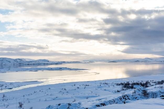 Winterpanorama mit schnee und eis auf see thingvellir islandblick