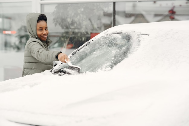Winterporträt der afrikanischen frau, die schnee von einem auto reinigt. frau in einer grünen jacke.