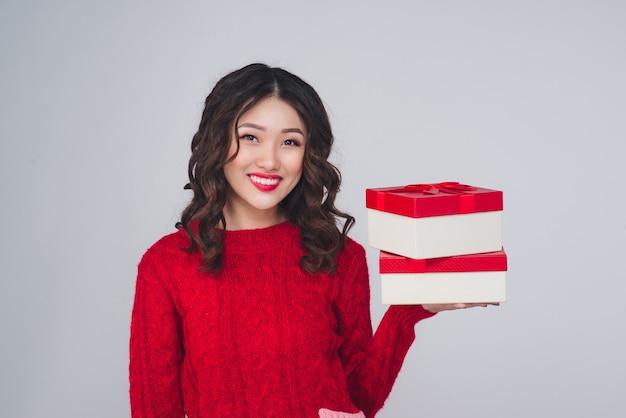 Winterporträt der asiatischen frau mit einem weihnachtsgeschenk. feiertage neues jahr.