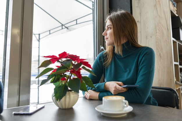 Winterporträt der frau, die am café mit tasse kaffee sitzt