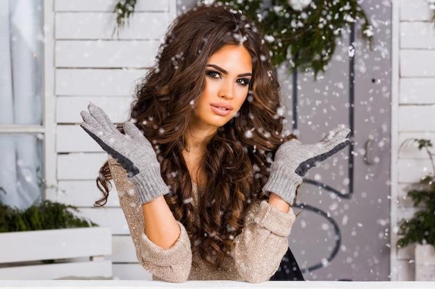 Winterporträt der jungen charmanten schönen brünetten frau, die warmen pullover mit schnee bedeckt trägt