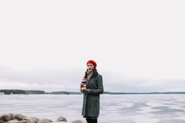 Winterporträt der jungen frau in einem mantel und im roten hut, die dekorativen leuchtturm halten und am ufer des gefrorenen meeres stehen. winter, reisen, meer hintergrund. windiges wetter, erstaunliche eisküste