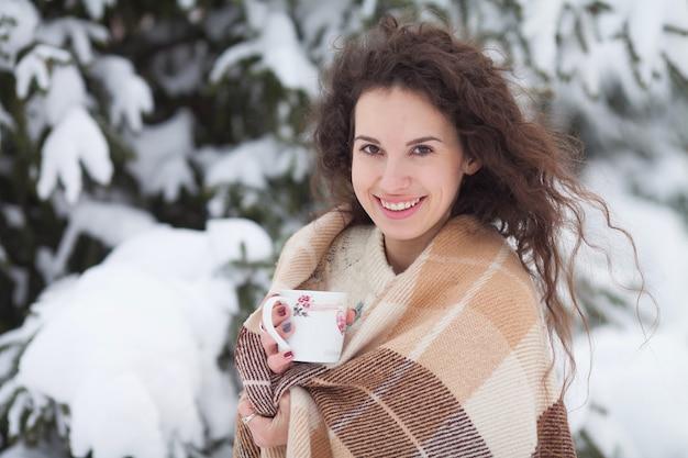 Winterporträt der jungen schönen brünetten frau, die gestrickten snood bedeckt im schnee trägt