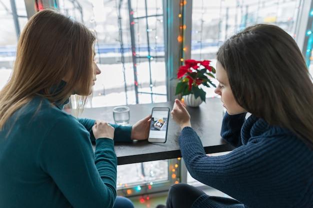Winterporträt der sprechenden jungen frauen, die in einem café sitzen