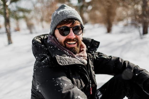 Winterporträt des hipster-mannes mit bart im grauen hut, der im sonnigen park mit schneeflocken auf kleidern entspannt