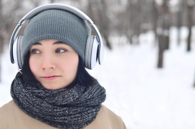 Winterporträt des jungen mädchens mit kopfhörern