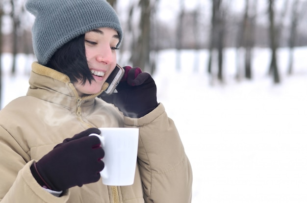 Winterporträt des jungen mädchens mit smartphone und kaffeetasse