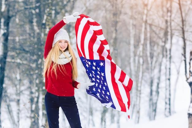Winterporträt des mädchens des jungen jugendlich mit usa-flagge. schönheits-frohes vorbildliches girl, das spaß im winterpark lacht und hat