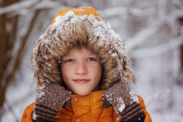 Winterporträt des netten kinderjungen in der gelben kleidung.
