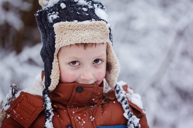 Winterporträt des netten kinderjungen in der warmen kleidung.