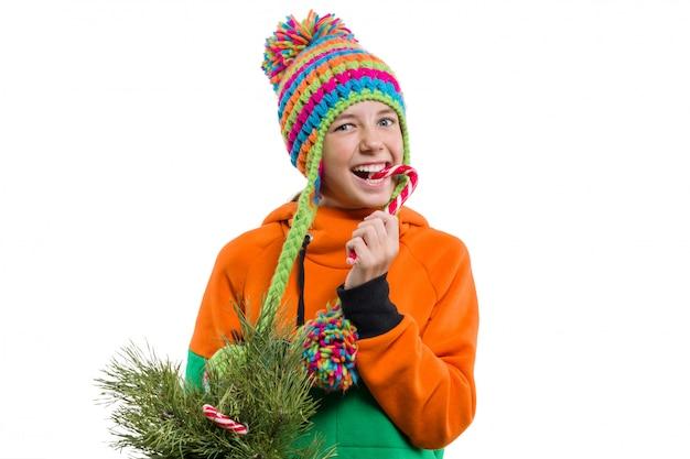 Winterporträt des netten mädchens mit weihnachtssüßigkeit