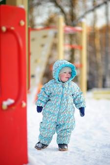 Winterporträt des schönen kleinkindjungen auf spielplatz