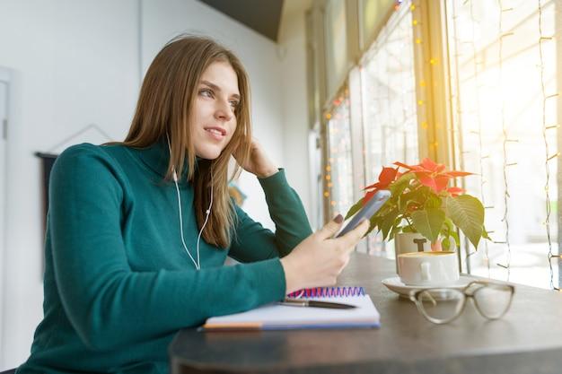 Winterporträt des studentenmädchens studierend im café