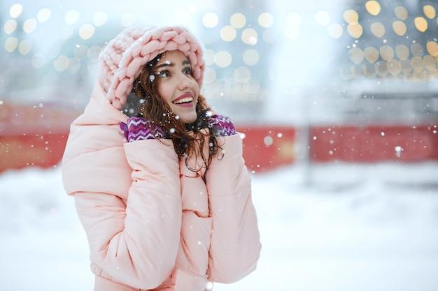 Winterporträt einer aufgeregten brünetten frau mit rosa mütze, die verschneites wetter genießt. freiraum