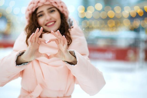 Winterporträt eines fröhlichen mädchens mit wintermantel und strickmütze, das herzgeste zeigt. freiraum