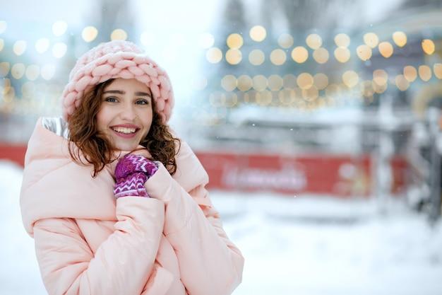 Winterporträt eines glücklich lächelnden mädchens mit rosa mantel und strickmütze, das in der nähe von straßenlaternen posiert. freiraum