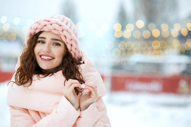 Winterporträt eines positiven mädchens mit wintermantel und strickmütze, das herzgeste zeigt. freiraum