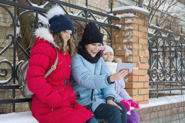 Winterporträt im freien der mutter und zwei töchter