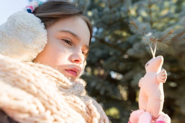 Winterporträt im freien des lächelnden mädchens nahe weihnachtsbaum