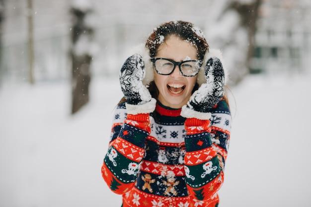 Winterporträt von tragenden ohrenschützern des jungen schönen mädchens, strickjacke, die im schneebedeckten park aufwirft. frau schaut und lächelt
