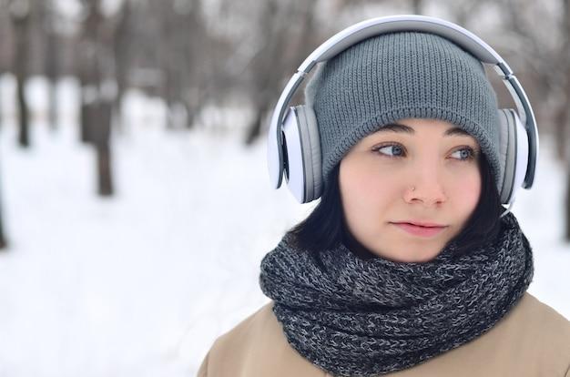Winterportrait des jungen mädchens mit kopfhörern