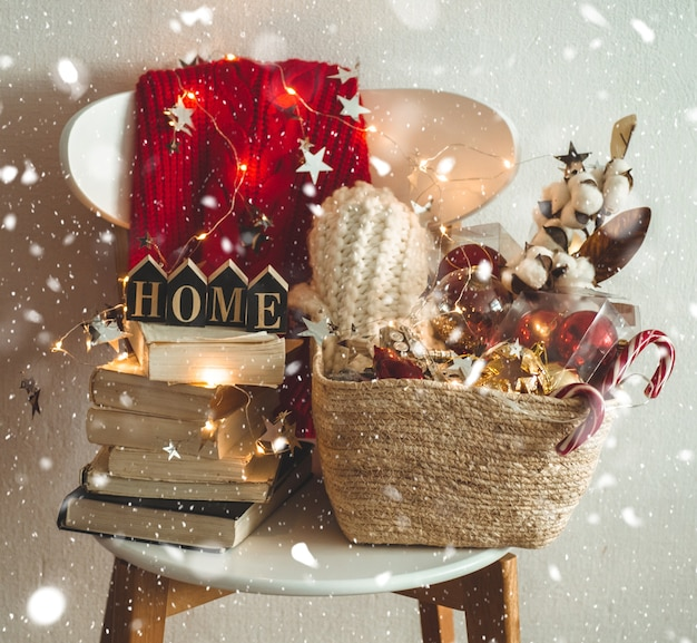 Winterpullover auf einem stuhl mit einem korb mit weihnachtsschmuck