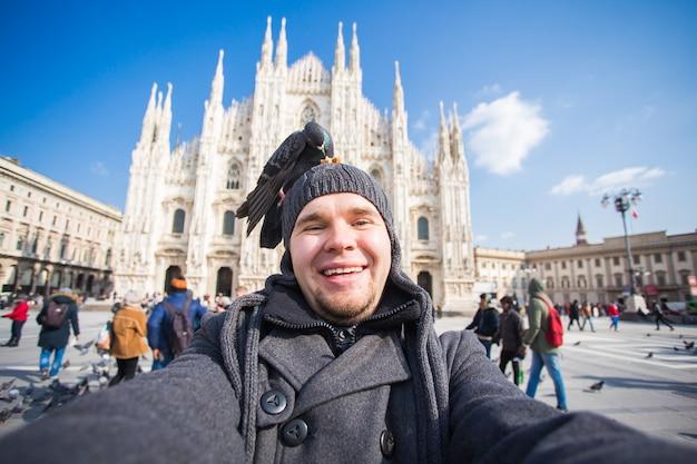 Winterreisen, urlaub und vogelkonzept - junger lustiger mann, der selfie mit tauben in der nähe des mailänder doms duomo di milano, italien, macht.