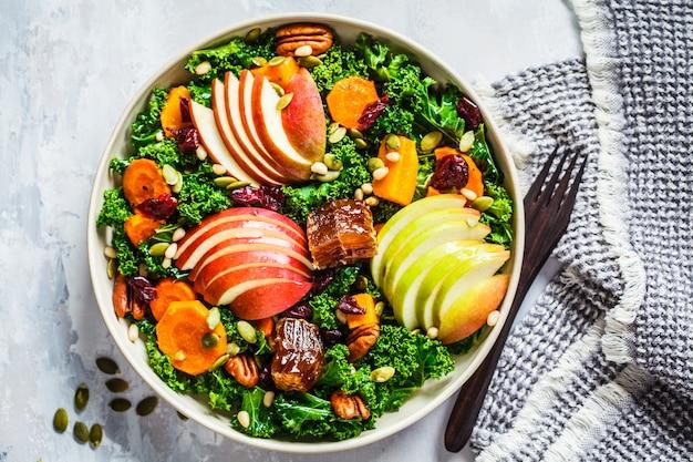 Wintersalat mit apfel, kürbis, preiselbeeren, honig und samen