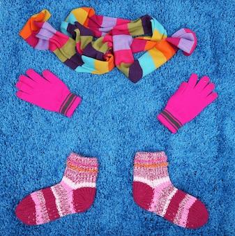 Winterschal, handschuhe und socken, auf farbiger oberfläche