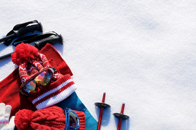 Winterschnee trägt hintergrund mit skistöcken, schutzbrillen, hüten und handschuhen mit copyspace zur schau.