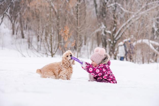 Winterspaß des kleinkindmädchens im rosa und cockerspaniel