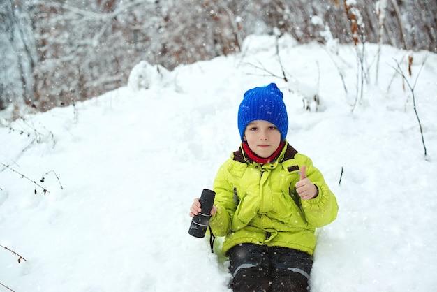 Winterspaß in der natur. netter kinderforscher im verschneiten wald. familienurlaub, verschneiter tag und glückliche kindheit.