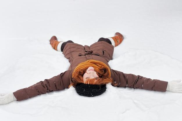 Winterspaß - schneeengel - junge schönheit, die im schnee spielt