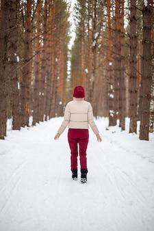 Winterspaziergang in einem schneebedeckten wald. ein mädchen mit rotem overall und jacke geht zwischen hohen bäumen in der natur spazieren.