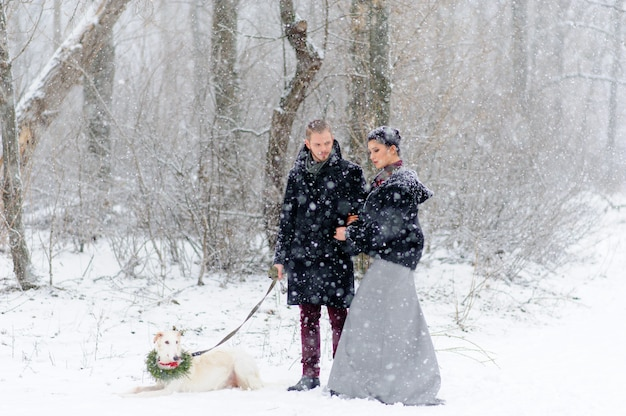 Winterspaziergang in einem schneesturm mit einem hund