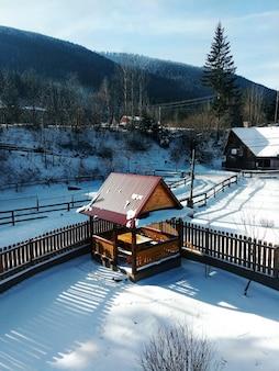 Wintersport-ski-konzept. landschaft des schneebedeckten waldes in bergen wenig haus am sonnigen tag