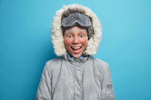 Wintersport- und freizeitkonzept. glückliche fröhliche aktive frau mit dem roten gefrorenen gesicht auf schneesturm, der nach dem skifahren zufrieden ist, hat spaß während des kalten tages auf der wanderreise gekleidet in der grauen jacke.