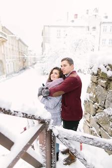 Winterstadt liebe. glückliche junge paare in den warmen strickjacken, die nahe dem gebäude in der winterstadt umarmen. wintermorgen und urlaub.