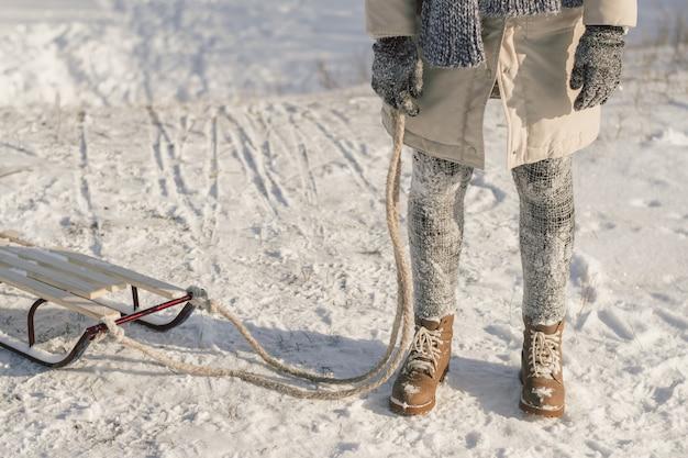 Winterstiefel auf schnee nahe schlitten mit seil.