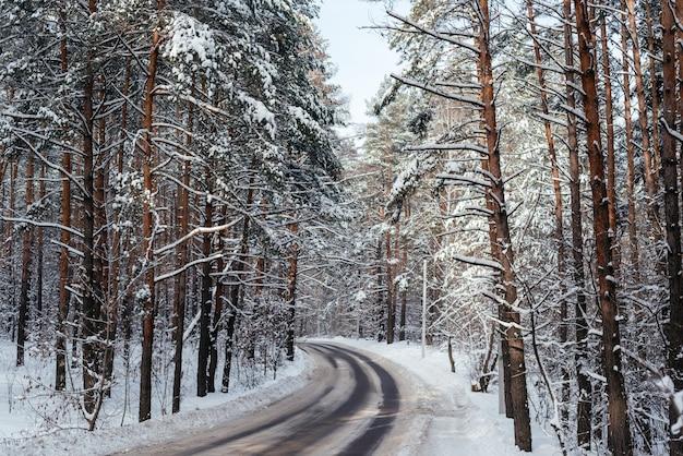 Winterstraße durch verschneiten wald, schöner winterhintergrund