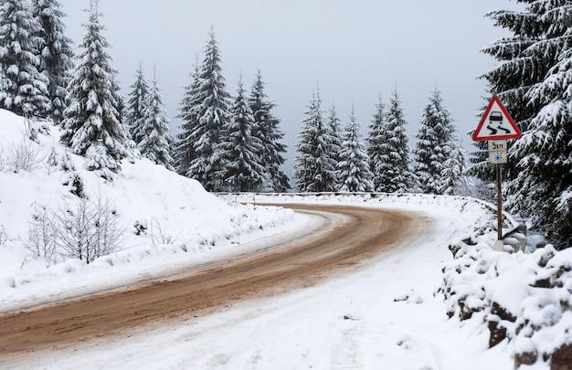 Winterstraße geht weg in die berge