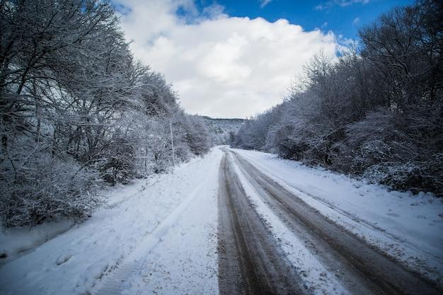 Winterstraße landstraße, die durch eine winterberglandschaft führt
