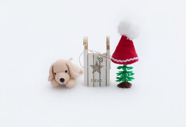 Winterurlaub hintergrund: kleiner plüschhund in weihnachtsmütze in der nähe von holzschlitten und kunststoff-weihnachtsbaum. nahaufnahme